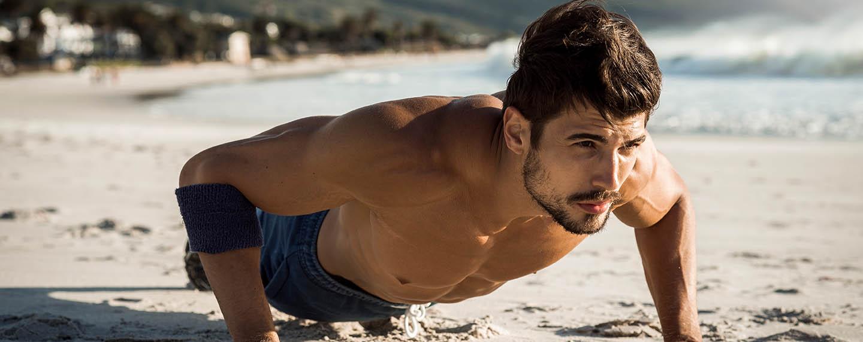 Man doing push-ups on the beach